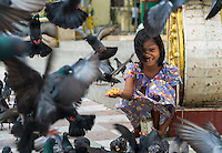 YANGON, MYANMAR - CIRCA DECEMBER 2013: Happy girl playing with pigeons in the streets of Yangon.