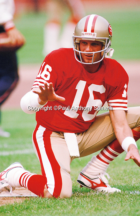San Francisco 49ers quarterback Joe Montana (16) catches a snap as the holder on a kick attempt during pregame warmups at the NFL football game against the Atlanta Falcons on Sept. 18, 1988 in Anaheim, Calif. The Falcons won the game 34-17. (©Paul Anthony Spinelli)