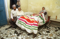 Family sitting in bedroom of home in Gobindigarh; Punjab; India,