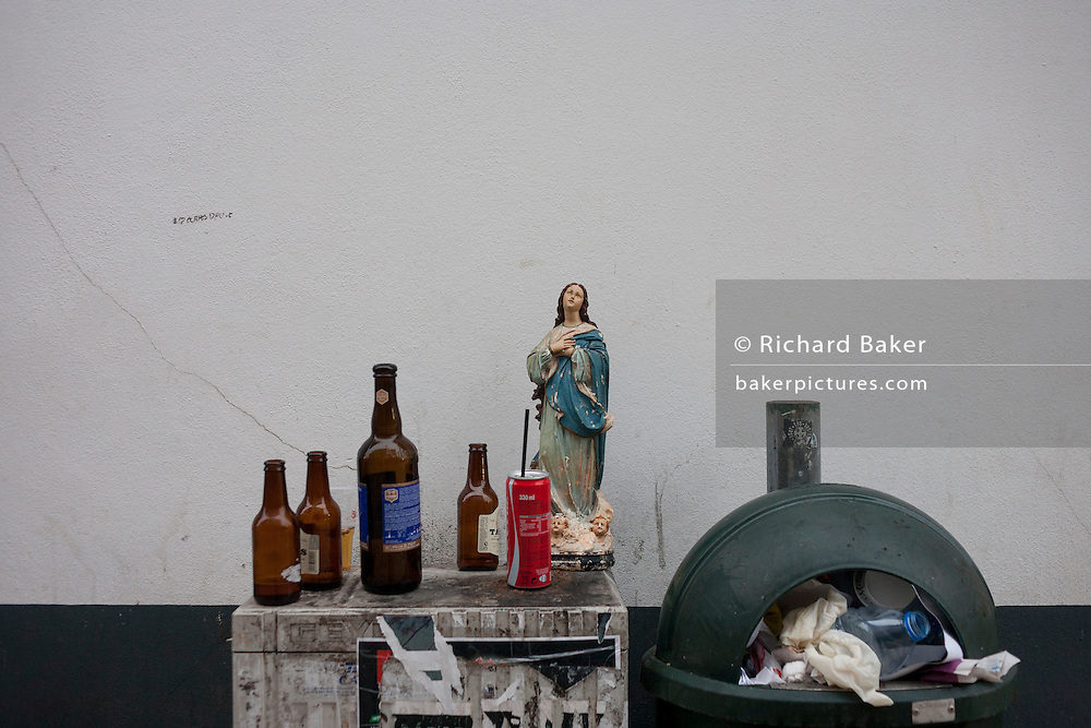 Jesus figurine surrounded by rubbish and alcohol early morning, in Aveiro, Portugal.
