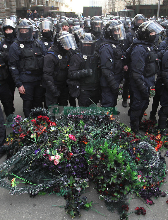 March 23, 2019 - Kiev, Kiev, Ukraine - Activists are seen throwing wreath flowers next to the riot police officers during the anti-corruption protest outside Presidential office in Kiev..Activists and supporters of ''National Corps'' Ukrainian nationalist party demand investigation and to arrests of top figures in an alleged military corruption scandal, which they were accused of profiting from the sale to state defence companies at inflated prices of smuggled Russian military parts. (Credit Image: © Pavlo Gonchar/SOPA Images via ZUMA Wire)