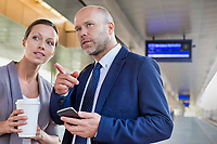 Portrait of businessman gesturing while talking to young attractive businesswoman in train station