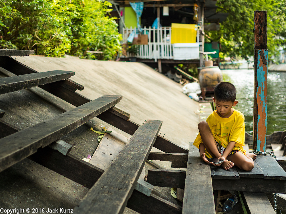 07 APRIL 2016 - BANGKOK, THAILAND: A boy watches videos on his smart phone near the khlong (canal) that runs behind the squatters' community at Mahakan Fort. Mahakan Fort was built in 1783 during the reign of Siamese King Rama I. It was one of 14 fortresses designed to protect Bangkok from foreign invaders, and only of two remaining, the others have been torn down. A community developed in the fort when people started building houses and moving into it during the reign of King Rama V (1868-1910). The land was expropriated by Bangkok city government in 1992, but the people living in the fort refused to move. In 2004 courts ruled against the residents and said the city could take the land. The final eviction notices were posted last week and the residents given until April 30 to move out. After that their homes, some of which are nearly 200 years old, will be destroyed.       PHOTO BY JACK KURTZ