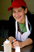 Happy teen age 17 waiting for customers in her fajita food stand. Grand Old Day Street Fair St Paul Minnesota USA