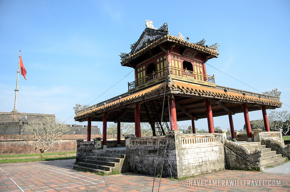 A pagoda across the moat at the Imperial City in Hue, Vietnam. A self-enclosed and fortified palace, the complex includes the Purple Forbidden City, which was the inner sanctum of the imperial household, as well as temples, courtyards, gardens, and other buildings. Much of the Imperial City was damaged or destroyed during the Vietnam War. It is now designated as a UNESCO World Heritage site. The citadel, with its large Vietnamese flag, is at the left of frame in the background.