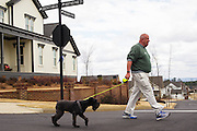 "HOOVER, AL – MARCH 1, 2016: Martin Ennis, 68, walking his dog Lucy in the Moss Rock Preserve neighborhood. ""I'm a conservative but not Republican,"" Ennis said. ""The last 8 years the progressives have taken over everything. We've gotten away from the constitution in many ways. Politics is about choices, not ideals. So if it's between trump and Clinton, yeah, I'm gonna vote for Trump. I worry, but that's what I'll do. And I feel conflicted in that because I feel he is not the answer.""<br /> <br /> On Super Tuesday, voters in the economically vibrant city of Hoover turned out to voice their support for a presidential candidate. Located in the Appalachian foothills, Hoover is the largest suburb of Birmingham and is home to several planned communities with idyllic neighborhoods tailored for the upper middle class. CREDIT: Bob Miller for The Wall Street Journal<br /> OLDCITIES"