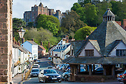 Motoring in a BMW saloon car through the old town of Dunster, Dunster Castle in background, in Somerset, UK
