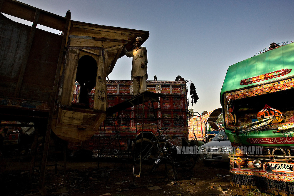 RAWALPINDI, PAKISTAN - OCTOBER 9: A worker stands on scaffolding next to a Bedford truck-tray under construction at a painting and repair yard, October 9, 2008, in Rawalpindi, Pakistan. The heavily adorned Bedford trucks have become a national icon and cost upwards of one million rupees (USD$12,500) for a full makeover. Much of the artwork consists of a cultural mix of religious and secular, Pakistani film and music stars, cricket legends, romanticized military imagery of F-16 fighter jets and Ghauri missiles, the Prophet's winged horse, Buraq, and dreamlike scenes of wooded lakes and snow-capped mountains and exotic animals. (Photo by Warrick Page)
