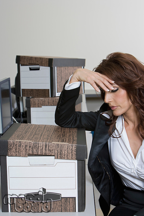 Stressed Businesswoman and Moving Boxes