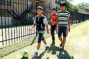 (L to R) Roshan Diyali (13), Yogesh Acharya (13), Roshan Biswa (13) walk to their homes in the Ivy Apartments where Thomas E. Duncan, the first confirmed Ebola virus patient in the United States, was staying with family in Dallas, Texas on October 4, 2014. Duncan is now being treated at Texas Health Presbyterian Hospital Dallas while members of his family have been isolated in the apartment. (Cooper Neill for The New York Times)