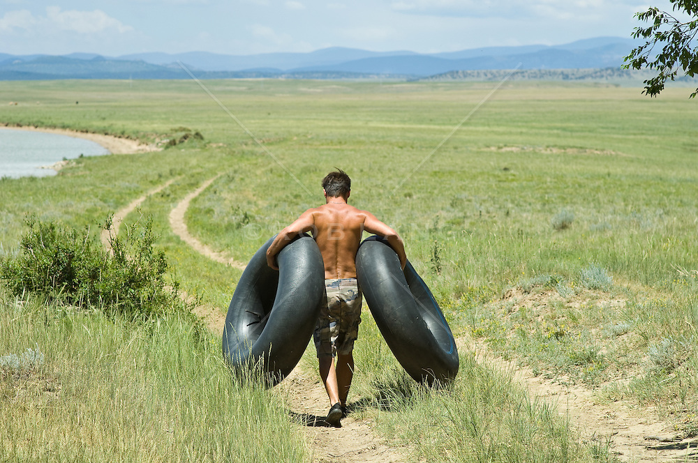 Man carrying two inner tubes down to the lake