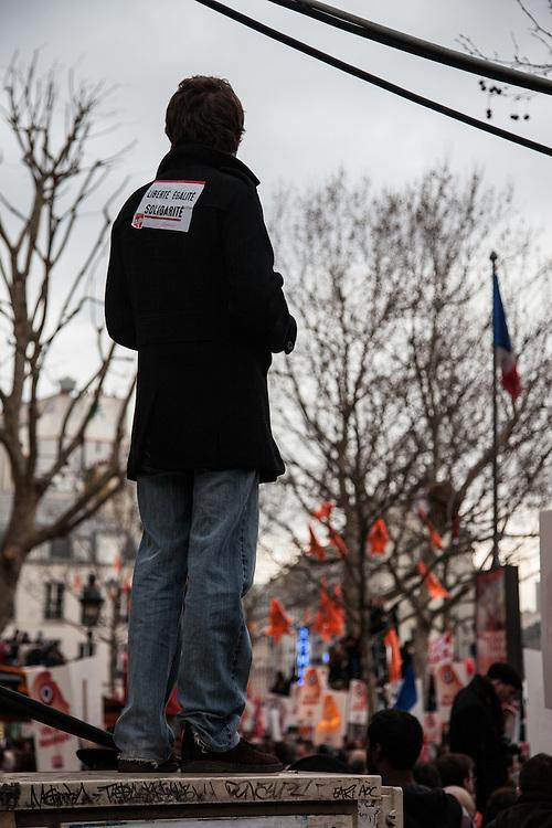 """Un homme porte sur son dos un autocollant """"Liberté, égalité, fraternité"""" et regarde la foule debout sur une borne électrique, lors du rassemblement du Front de Gauche, le 18 mars 2012 à la Bastille."""