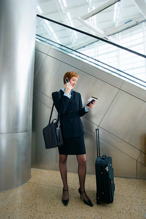 A red haired late 20's / early 30's Caucasian business woman looks at her travel documents while talking on her cell phone while standing in an airport with her luggage..20050916_MR_C.20050916_PR_A
