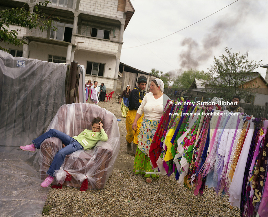 """Isabella Mihai sits bored on an armchair which is part of the dowry presents (along with the rack of scarves) of her elder sister Garoafa, on the day of Garoafa's wedding to Florin 'Ciprian' Lulu,  in the village of Sintesti, in Romania, Sunday, Sept. 24, 2006.  The dowry gifts are brought from Garoafa's family's home to be displayed along the roadside, for all the village to see. For the wedding 100 pigs, costing approximately 30,000 USD, were slaughtered. Garoafa wore a gold """"salbe""""- a necklace of gold Franz Josef coins, worth an estimated 30,000 USD. The Kalderari roma of Sintesti are by tradition metal workers, originally making alcohol stills, pots and pans, but now dealing in scrap metal ( the smoke in the background comes from a metal furnace). The large profits from their business have enabled them to build large houses in the village of Sintesti, 20km from Bucharest, and to invest in fast, Western brand name cars such as BMW's, Mercedes and Porsche."""
