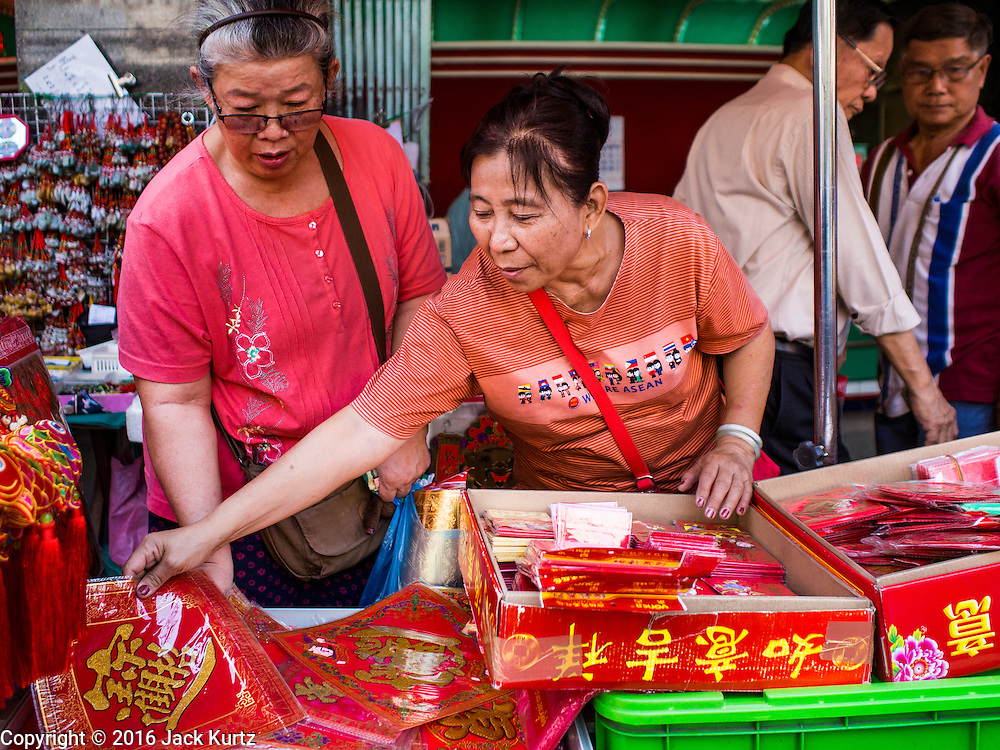 """04 FEBRUARY 2016 - BANGKOK, THAILAND: People shop for Chinese New Year supplies in Bangkok's Chinatown district, before the celebration of the Lunar New Year. Chinese New Year, also called Lunar New Year or Tet (in Vietnamese communities) starts Monday February 8. The coming year will be the """"Year of the Monkey."""" Thailand has the largest overseas Chinese population in the world; about 14 percent of Thais are of Chinese ancestry and some Chinese holidays, especially Chinese New Year, are widely celebrated in Thailand.      PHOTO BY JACK KURTZ"""