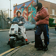 Two teenage boys one on his scooter the other leaning against a lamp post, Hackney, East London, 2000's