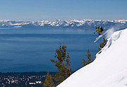 Skier jumping off the top of Incline Peak with Lake Tahoe in the background near the Mt. Rose Summit.