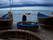A fisherman prepares his net early in the morning in Mui Nai...In Vietnam fisheries are a large part the country's economy with fisheries that produce over 100 species of fish.  Industry practices range from a lone fisherman on a small boat to large vessels with hundreds of people frantically working together to unload, sort, and transport fish to local and distant markets.