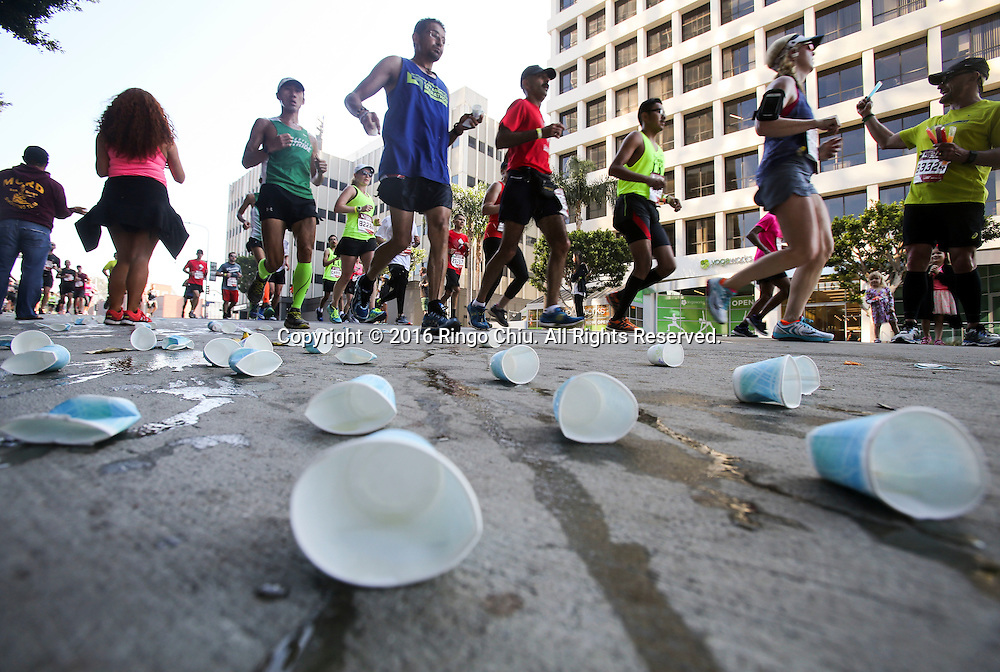 Runners pass through a water station along Wilshire Boulevard during the 31st Los Angeles Marathon in Los Angeles, Sunday, Feb. 14, 2016. The 26.2-mile marathon started at Dodger Stadium and finished at Santa Monica.  (Photo by Ringo Chiu/PHOTOFORMULA.com)<br /> <br /> Usage Notes: This content is intended for editorial use only. For other uses, additional clearances may be required.