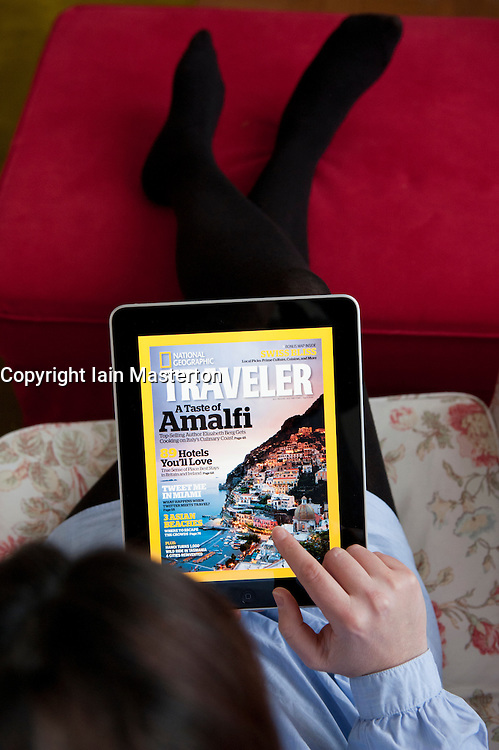 woman looking at National Geographic Traveler travel magazine application on an iPad tablet computer