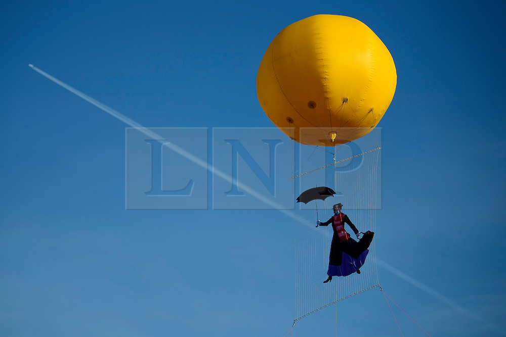 © Licensed to London News Pictures. 06/01/2017. London, UK. A plane flies behind an image of Mary Poppins wearing a face mask, suspended from a balloon over Parliament Square in London during a protest about air pollution by Greenpeace.. Photo credit: Ben Cawthra/LNP