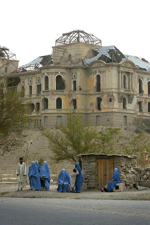 Women wearing burkas wait for a bus in front of the destroyed National Palace.<br />
