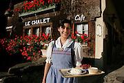 """La Gruyère doit sa réputation pour beaucoup à ses excellents produits gastronomiques, ses fromages, les meiringues et la double crème. La région et la ville de Gruyères sont visités chaque année par des centaines de milliers de touristes. Le tourisme est aujourd'hui une partie intégrante de l'économie du district. Mais pour fonctionner le secteur a besoin, comme l'agriculture et l'industrie, d'une main d'oeuvre étrangère. Comme au restaurant """"Le Châlet"""" à Gruyères ou le client est servi par des saisonnières portugaises en costume traditionel. Madame Fernanda Costa, Gruyères, août 2005. © Romano P. Riedo"""