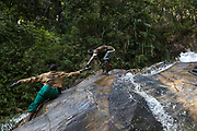 Tik and Chae navigate a steep and slippery waterfall on a 3 day hunting trip deep in the forest.<br /> <br /> Evidence suggests that the Maniq, a Negrito tribe of hunters and gatherers, have inhabited the Malay Peninsula for around 25,000 years. Today a population of approximately 350 maniq remain, marooned on a forest covered mountain range in Southern Thailand. Whilst some have left their traditional life forming small villages, the majority still live the way they have for millennia, moving around the forest following food sources. <br /> <br /> Quiet and reclusive they are little known even in Thailand itself but due to rapid deforestation they are finding it harder to survive on the forest alone and are slowly being forced to move to its peripheries closer to Thai communities.