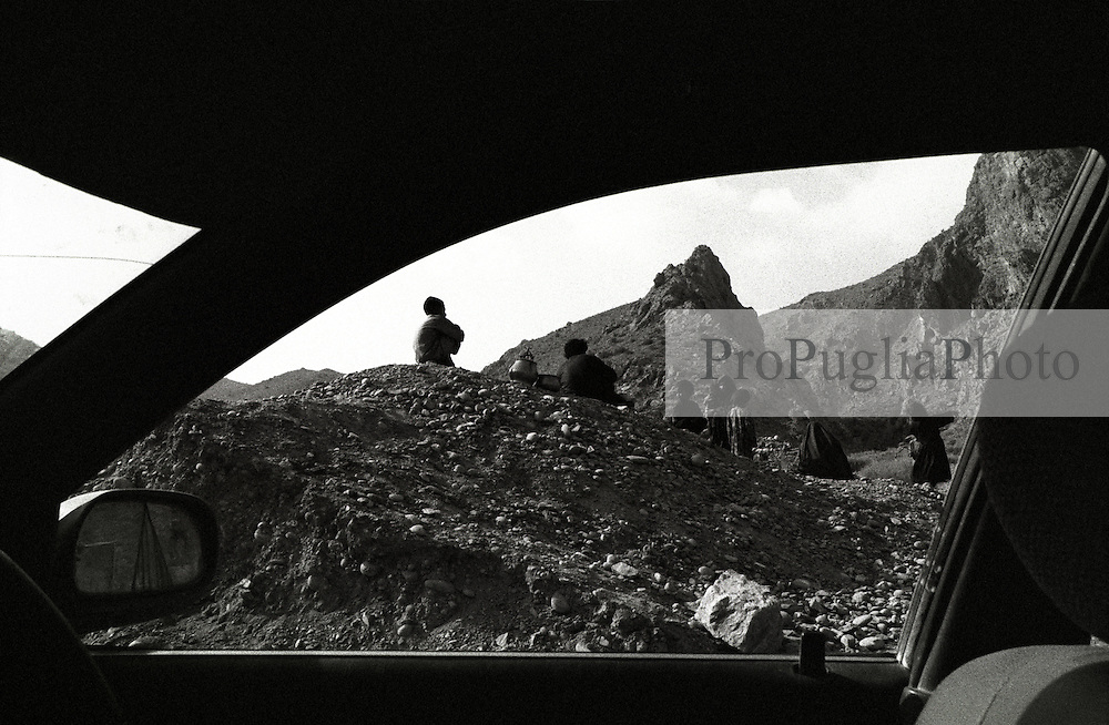On the road to Torkham. Children with mothers on a rocky crag near theri village
