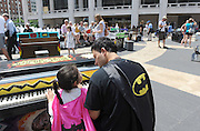 Warren Alvarez and his daughter Delilah, 5, of Queens, enjoy Father's Day by playing one of the 88 Sing for Hope Pianos, supported by Chobani, Inc., at the Josie Robertson Plaza at Lincoln Center, Sunday, June 16, 2013, in New York.  The event celebrates the conclusion of the Sing for Hope Pianos project, a two-week public art installation around the five boroughs of New York.  (Photo by Diane Bondareff/Invision for Sing for Hope)