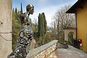 Sculpture at the rear of La Prioria, home of Gabriele D'Annunzio, 1863-1938, Italian writer, soldier and fascist, at Vittoriale degli italiani, or The Shrine of Italian Victories, his estate and museums at Gardone Riviera, Lake Garda, Brescia, Lombardy, Italy. The house was originally the Villa Cargnacco, which was rebuilt by Gian Carlo Maroni from 1922 and developed until 1955. In the background is the Regia Nave Puglia, a warship, set into the Mastio hill, a gift from Admiral Thaon di Revel in 1923. Inside the ship is the Onboard Museum, opened 2002, with models of warships belonging to Duke Amedeo d'Aosta. The estate consists of the Prioria, where d'Annunzio lived 1922-38, an amphitheatre, the protected cruiser Puglia, the MAS vessel used by D'Annunzio in 1918 and a mausoleum. It is part of the Grandi Giardini Italiani. Picture by Manuel Cohen