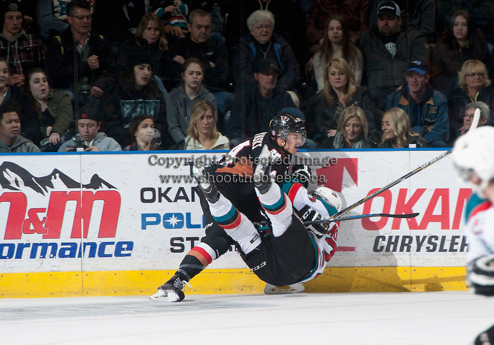 KELOWNA, CANADA - FEBRUARY 28: Carsen Twarynski #24 of Calgary Hitmen checks Josh Morrissey #27 of Kelowna Rockets to the ice during the second period on February 28, 2015 at Prospera Place in Kelowna, British Columbia, Canada.  (Photo by Marissa Baecker/Shoot the Breeze)  *** Local Caption *** Carsen Twarynski; Josh Morrissey;