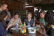ICS volunteers gather in a local cafe for lunch in the village of in Banteay Char, near Battambang, Cambodia.