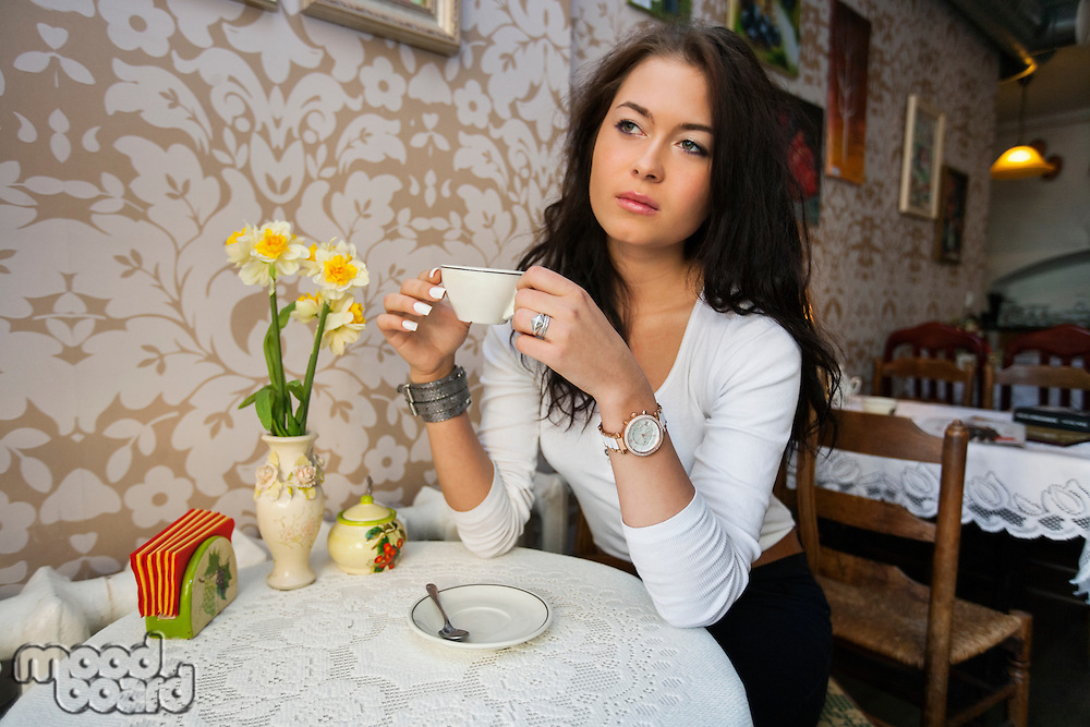 Thoughtful young woman having coffee at cafe