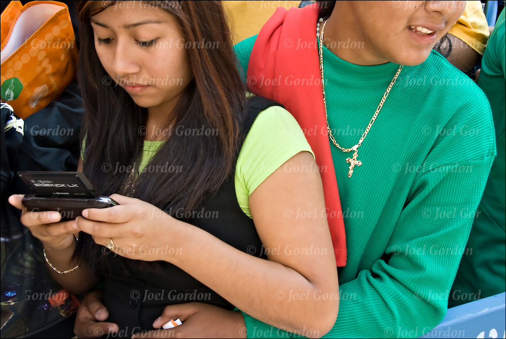 Young Hispanic American teen in crowd instead of watching the Mexican Day Parade she is using her cellphone to text message her friends.