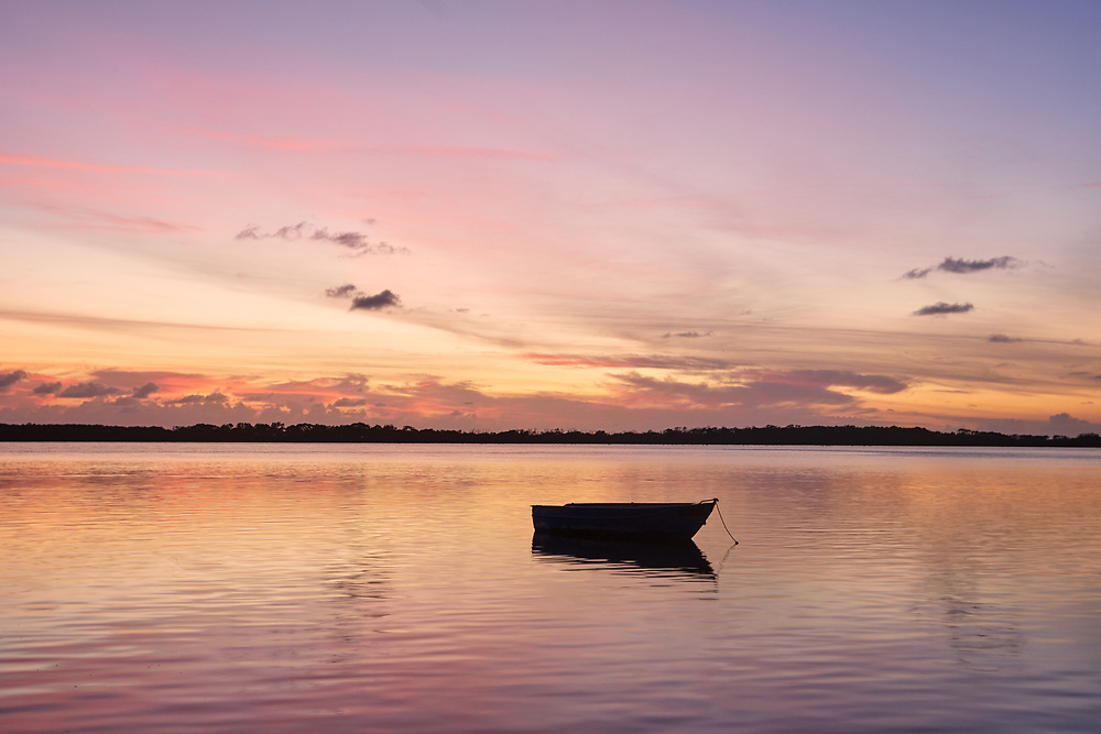 A lone boat on Pumicestone Passage at sunrise.