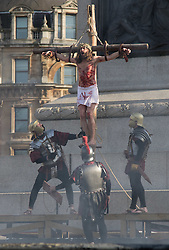 Trafalgar Square, London, March 25th 2016. Thousands of Londoners an tourists in Trafalgar Square are treated to The Passion of Jesus, a re-enactment of the events leading up to the crucifixion and resurrection of Jesus Christ. PICTURED: Roman soldiers hammer jesus's feet to the cross. <br /> &copy;Paul Davey<br /> FOR LICENCING CONTACT: Paul Davey +44 (0) 7966 016 296 paul@pauldaveycreative.co.uk