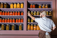Sous Chef Evan VanHorn collects jars of pickled items from the shelves at The Grocery.