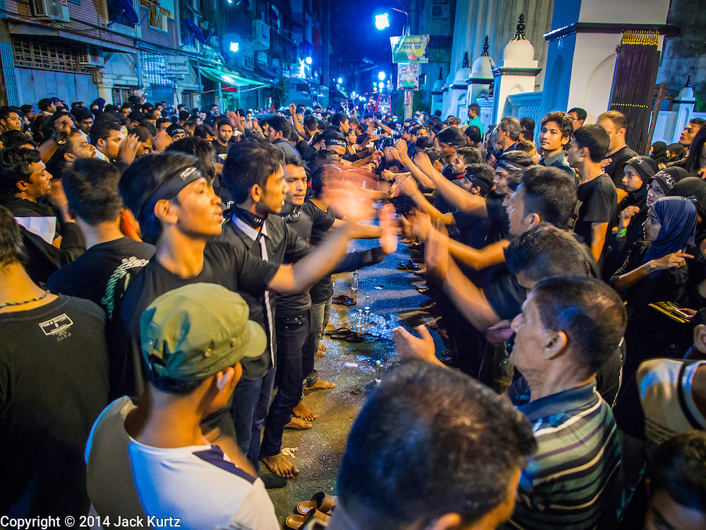 04 NOVEMBER 2014 - YANGON, MYANMAR: Burmese men pound their chests and chat prayers to Hussein ibn Ali on Ashura in Yangon. Ashura commemorates the death of Hussein ibn Ali, the grandson of the Prophet Muhammed, in the 7th century. Hussein ibn Ali is considered by Shia Muslims to be the third imam and the rightful successor of Muhammed. He was killed at the Battle of Karbala in 610 CE on the 10th day of Muharram, the first month of the Islamic calendar. According to Myanmar government statistics, only about 4% of the population is Muslim. Many Muslims have fled Myanmar in recent years because of violence directed against Burmese Muslims by Buddhist nationalists.    PHOTO BY JACK KURTZ