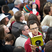 A reveler reads a book entitled 'The Meaning of the 21st Century' in the early morning hours before the wedding of Prince William and Kate Middleton at Westminster Abbey.