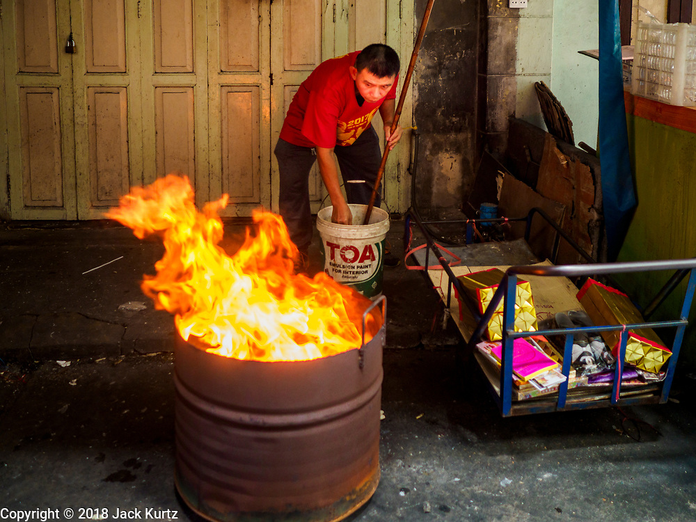"15 FEBRUARY 2018 - BANGKOK, THAILAND:  A man burns ""ghost money"" for Tet in front of his home in Bangkok's Chinatown. Lunar New Year, also called Tet or Chinese New Year, is 16 February this year. The coming year will be the Year of the Dog. Thailand has a large Chinese community and Lunar New Year is widely celebrated in Thailand, especially in Bangkok and large cities with significant Chinese communities.    PHOTO BY JACK KURTZ"