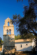 The stone belltower of Agios Constantinos surrounded by olive trees.<br /> Paxos, Ionian Islands, Greece