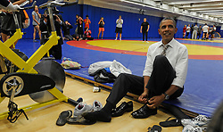 While making a stop at the Olympic Training Center in Colorado Springs, Colorado, USA, President Obama puts on his shoes after removing them to walk on the wrestling mat on Thursday, Aug. 9, 2012. Photo by Jerilee Bennett/Colorado Springs Gazette/MCT/ABACAPRESS.COM  | 330672_001 Colorado Springs Etats-Unis United States