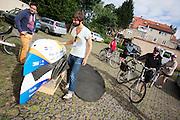 Het team maakt de VeloX4 gereed, terwijl andere gasten van het pension geinteresseerd kijken. Het Human Power Team Delft en Amsterdam (HPT), dat bestaat uit studenten van de TU Delft en de VU Amsterdam, is in Senftenberg voor een poging het uurrecord te verbreken op de Dekrabaan. In september wil het HPT daarna een poging doen het wereldrecord snelfietsen te verbreken, dat nu op 133 km/h staat tijdens de World Human Powered Speed Challenge.<br /> <br /> Guest of the hotel look at the students preparing the bike. With the special recumbent bike the Human Power Team Delft and Amsterdam, consisting of students of the TU Delft and the VU Amsterdam, is in Senftenberg (Germany) for the attempt to set a new hour record on a bicycle. They also wants to set a new world record cycling in September at the World Human Powered Speed Challenge. The current speed record is 133 km/h.