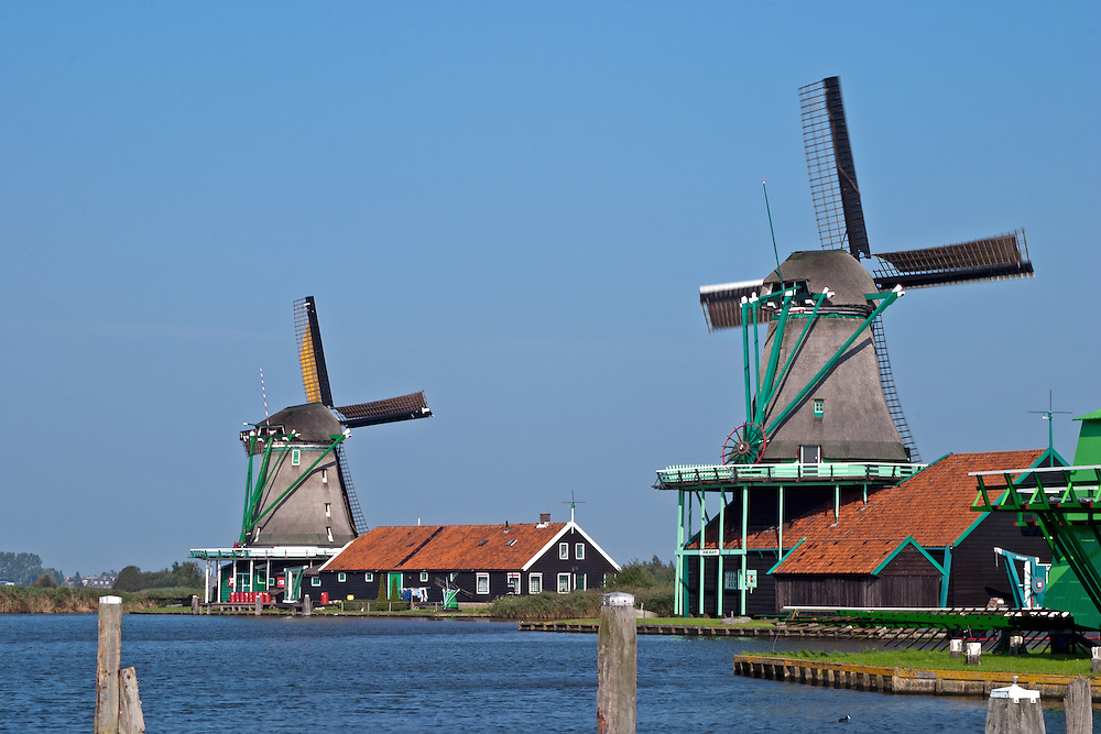 """Two of Zaanse Schans' working windmills, part of an extensive outdoor museum, are a popular day trip for Amsterdam visitors.  .From Wikipedia: """" Zaanse Schans is a neighbourhood of Zaandam, near Zaandijk in the municipality of Zaanstad in the Netherlands, in the province of North Holland. It has a collection of well-preserved historic windmills and houses; the ca. 35 houses from all over the Zaanstreek were moved to the museum area in the 1970s. The Zaans Museum, established in 1994, is located in the Zaanse Schans..The Zaanse Schans is one of the popular tourist attractions of the region and an anchor point of ERIH, the European Route of Industrial Heritage. The neighbourhood attracts approximately 900,000 visitors every year..The windmills were built after 1574."""".Also from Wikipedia: """" Along the river Zaan, you can find still dozens of original windmills (mostly entirely made of wood), still technically functioning, some of them over 350 years old. Next to these there are many 19th century stone industrial buildings, nowadays derelict or converted into apartments, but still recognisable as industrial buildings.""""."""