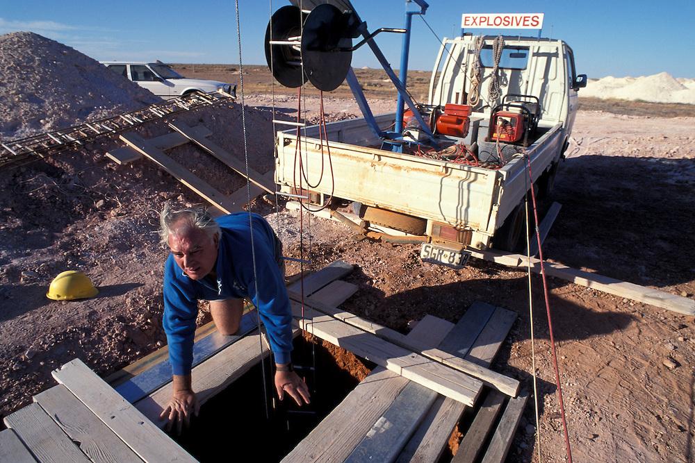 Australia, South Australia, (MR) Stuart Bird peers into 100' deep opal mine shaft in Coober Pedy.