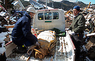 Japanese forces remove a dead body in the town of Kirikiri after the earthquake and tsunami hit the city on 11 March 2011.