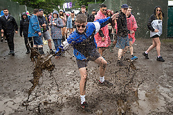 © Licensed to London News Pictures . 11/06/2016 . Manchester , UK . A reveller splashes through a muddy puddle at the Parklife music festival at Heaton Park in Manchester . Photo credit : Joel Goodman/LNP
