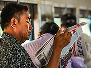 26 OCTOBER 2015 - YANGON, MYANMAR: A man reads a newspaper on the Yangon Circular Train. The Yangon Circular Railway is the local commuter rail network that serves the Yangon metropolitan area. Operated by Myanmar Railways, the 45.9-kilometre (28.5 mi) 39-station loop system connects satellite towns and suburban areas to the city. The railway has about 200 coaches, runs 20 times daily and sells 100,000 to 150,000 tickets daily. The loop, which takes about three hours to complete, is a popular for tourists to see a cross section of life in Yangon. The trains run from 3:45 am to 10:15 pm daily. The cost of a ticket for a distance of 15 miles is ten kyats (~nine US cents), and for over 15 miles is twenty kyats (~18 US cents).    PHOTO BY JACK KURTZ