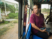"13 MAY 2015 - MAHACHAI, SAMUT SAKHON, THAILAND: A passenger in a ""songthaew"" running from Samut Sakhon to Samut Songkram. Songthaew means literally ""two rows."" It is a passenger vehicle in Thailand and Laos adapted from a pick-up or a larger truck and used as a share taxi.    PHOTO BY JACK KURTZ"